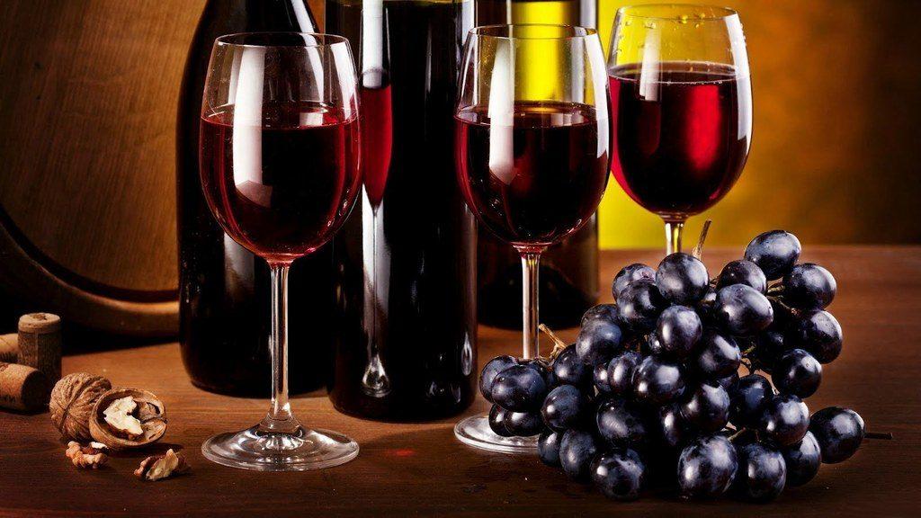beneficios-del-vino-tinto-botellas-con-uvas