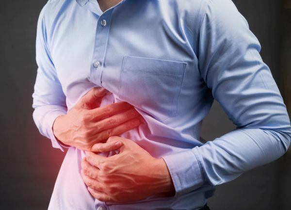 enfermedad-de-crohn-hombre-camisa-azul-dolor