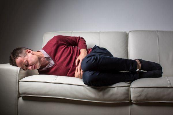 que-es-la-enfermedad-de-crohn-hombre-tendido-en sofa-dolor